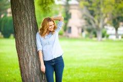 Όμορφη νέα γυναίκα που στέκεται δίπλα σε ένα δέντρο Στοκ Φωτογραφία