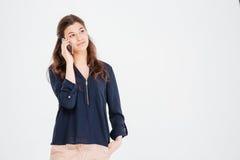 Όμορφη νέα γυναίκα που στέκεται και που χρησιμοποιεί το κινητό τηλέφωνο στοκ φωτογραφία