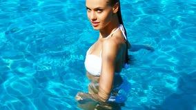 Όμορφη νέα γυναίκα που στηρίζεται στην πισίνα απόθεμα βίντεο