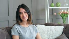 Όμορφη νέα γυναίκα που στηρίζεται στον καναπέ στο σπίτι camera girl looking portrait smiling απόθεμα βίντεο
