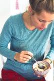 όμορφη νέα γυναίκα που τρώει τα δημητριακά για το πρόγευμα στην πυτζάμα της στοκ φωτογραφία