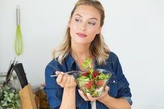 Όμορφη νέα γυναίκα που τρώει τη σαλάτα στο σπίτι Στοκ εικόνα με δικαίωμα ελεύθερης χρήσης