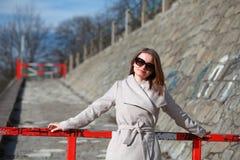 Όμορφη νέα γυναίκα που φορά ένα παλτό μια ηλιόλουστη χειμερινή ημέρα Στοκ Εικόνες