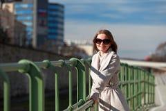 Όμορφη νέα γυναίκα που φορά ένα παλτό μια ηλιόλουστη χειμερινή ημέρα Στοκ Φωτογραφίες