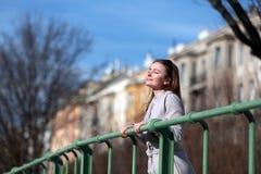 Όμορφη νέα γυναίκα που φορά ένα παλτό μια ηλιόλουστη χειμερινή ημέρα στοκ εικόνα
