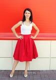 Όμορφη νέα γυναίκα που φορά μια κόκκινη φούστα πέρα από ζωηρόχρωμο στοκ φωτογραφία
