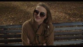 Όμορφη νέα γυναίκα που φορά τα γυαλιά ηλίου που κάθονται σε έναν πάγκο στο πάρκο φθινοπώρου φιλμ μικρού μήκους