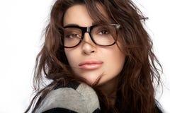 Όμορφη νέα γυναίκα που φορά τα καθιερώνοντα τη μόδα γυαλιά στοκ φωτογραφία