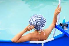 Όμορφη νέα γυναίκα που φορά τη ριγωτά συνεδρίαση και το relaxi καπέλων ήλιων Στοκ Εικόνα
