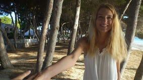 Όμορφη νέα γυναίκα που φορά το άσπρο χέρι εκμετάλλευσης φορεμάτων και που οδηγεί το φίλο της στην αποβάθρα απόθεμα βίντεο
