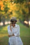 Όμορφη νέα γυναίκα που φορά το καπέλο αχύρου ND glassea ήλιων που μιλά το ο Στοκ Εικόνες
