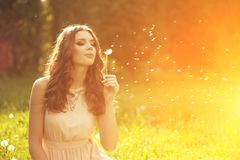 Όμορφη νέα γυναίκα που φυσά μια πικραλίδα Καθιερώνον τη μόδα νέο κορίτσι Στοκ εικόνα με δικαίωμα ελεύθερης χρήσης