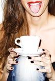 Όμορφη νέα γυναίκα που χαμογελά, γλώσσα έξω, που κρατά τον καφέ, καλλιτεχνικό υψηλό κλειδί στοκ φωτογραφία με δικαίωμα ελεύθερης χρήσης