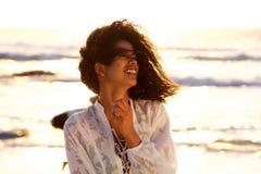 Όμορφη νέα γυναίκα που χαμογελά στην παραλία κατά τη διάρκεια του ηλιοβασιλέματος Στοκ Εικόνες