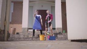 Όμορφη νέα γυναίκα που χορεύει και που τραγουδά στο μέρος του σπιτιού ενώ τα ψεκάζοντας απορρυπαντικά συζύγων της Καθαρισμός απόθεμα βίντεο