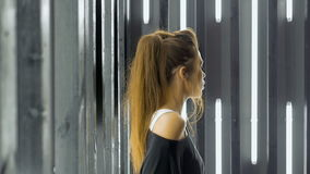 Όμορφη νέα γυναίκα που χορεύει σε ένα νυχτερινό κέντρο διασκέδασης, που ακούει τη μουσική μέσω των ακουστικών Τραγουδά ένα τραγού απόθεμα βίντεο