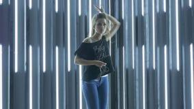 Όμορφη νέα γυναίκα που χορεύει σε ένα νυχτερινό κέντρο διασκέδασης, που ακούει τη μουσική μέσω των ακουστικών Γρήγορος ενεργητικό απόθεμα βίντεο