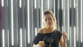 Όμορφη νέα γυναίκα που χορεύει σε ένα νυχτερινό κέντρο διασκέδασης, που ακούει τη μουσική μέσω των ακουστικών κίνηση αργή φιλμ μικρού μήκους
