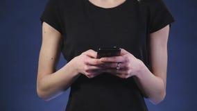 Όμορφη νέα γυναίκα που χρησιμοποιεί το έξυπνο τηλέφωνο με το μαύρο υπόβαθρο απόθεμα βίντεο