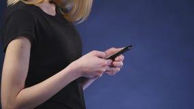 Όμορφη νέα γυναίκα που χρησιμοποιεί το έξυπνο τηλέφωνο με το μαύρο υπόβαθρο φιλμ μικρού μήκους