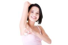Όμορφη νέα γυναίκα που χρησιμοποιεί το ανθιδρωτικό Στοκ Φωτογραφία