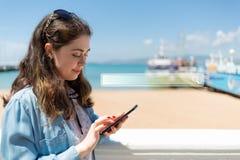 Όμορφη νέα γυναίκα που χρησιμοποιεί το κινητό τηλέφωνο Θάλασσα και σκάφη στο υπόβαθρο Κενό για το διάστημα αντιγράφων Έννοια της  στοκ εικόνες