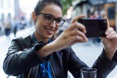 Όμορφη νέα γυναίκα που χρησιμοποιεί το κινητό τηλέφωνό της στην οδό Στοκ εικόνα με δικαίωμα ελεύθερης χρήσης