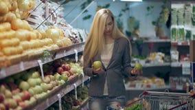 Όμορφη νέα γυναίκα που ψωνίζει σε ένα μανάβικο ή μια υπεραγορά απόθεμα βίντεο