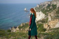 Όμορφη νέα γυναίκα σε έναν απότομο βράχο επάνω από τη θάλασσα, φύση Στοκ Εικόνες