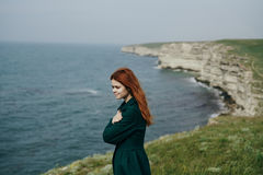 Όμορφη νέα γυναίκα σε έναν απότομο βράχο επάνω από τη θάλασσα, φύση Στοκ Εικόνα