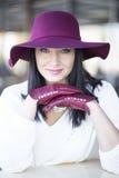 Όμορφη νέα γυναίκα σε ένα άσπρο σακάκι, burgundy ένα καπέλο και τα γάντια Στοκ Εικόνες