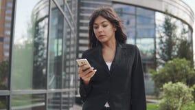 Όμορφη νέα γυναίκα σε ένα επιχειρησιακό κοστούμι που χρησιμοποιεί ένα smartphone επιχειρησιακή γυναίκα που ένα μήνυμα σε ένα κινη απόθεμα βίντεο