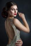 Όμορφη νέα γυναίκα σε ένα κρύσταλλο φορεμάτων βραδιού Τέλεια ομορφιά, κόκκινα χείλια, φωτεινό makeup Αστράφτοντας λαμπιρίζοντας π Στοκ Εικόνες