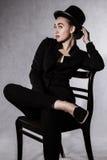 Όμορφη νέα γυναίκα σε ένα μαύρο καπέλο και ένα μαύρο σακάκι Στοκ εικόνες με δικαίωμα ελεύθερης χρήσης