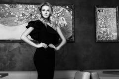 Όμορφη νέα γυναίκα σε ένα μαύρο φόρεμα βραδιού μαύρο λευκό Στοκ φωτογραφία με δικαίωμα ελεύθερης χρήσης