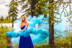 Όμορφη νέα γυναίκα σε ένα σύννεφο ενός φωτεινού μπλε καπνού Στοκ Εικόνα