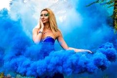 Όμορφη νέα γυναίκα σε ένα σύννεφο ενός φωτεινού μπλε καπνού Στοκ φωτογραφίες με δικαίωμα ελεύθερης χρήσης