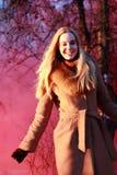 Όμορφη νέα γυναίκα σε ένα σύννεφο ενός φωτεινών κόκκινων καπνού και ενός ήλιου στοκ εικόνες