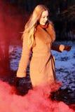 Όμορφη νέα γυναίκα σε ένα σύννεφο ενός φωτεινών κόκκινων καπνού και ενός ήλιου Στοκ Φωτογραφία