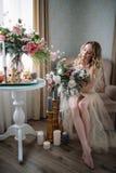 Όμορφη νέα γυναίκα σε ένα φόρεμα σπιτιών στο μπουντουάρ, που διακοσμείται με τα όμορφα λουλούδια, που κάθονται σε ένα άσπρο κρεβά Στοκ Φωτογραφία