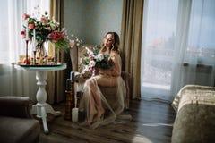 Όμορφη νέα γυναίκα σε ένα φόρεμα σπιτιών στο μπουντουάρ, που διακοσμείται με τα όμορφα λουλούδια, που κάθονται σε ένα άσπρο κρεβά Στοκ φωτογραφία με δικαίωμα ελεύθερης χρήσης