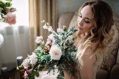 Όμορφη νέα γυναίκα σε ένα φόρεμα σπιτιών στο μπουντουάρ, που διακοσμείται με τα όμορφα λουλούδια, που κάθονται σε ένα άσπρο κρεβά Στοκ Εικόνα