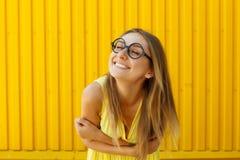Όμορφη νέα γυναίκα στα αστεία γυαλιά παιχνιδιών που χαμογελά άνω του κίτρινου β στοκ εικόνες