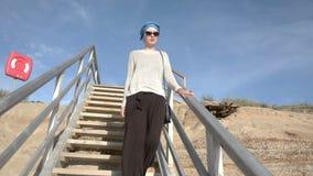 Όμορφη νέα γυναίκα στα γυαλιά ηλίου και τουρμπάνι που περπατά κάτω από τα σκαλοπάτια στην παραλία φιλμ μικρού μήκους