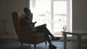 Όμορφη νέα γυναίκα στα γυαλιά που κάθονται στην κίτρινη καρέκλα και που χρησιμοποιούν το smartphone, που λειτουργεί από το κινητό απόθεμα βίντεο