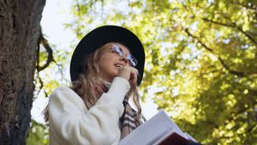 Όμορφη νέα γυναίκα στα μοντέρνα γυαλιά ηλίου που γράφουν κάποια σκέψη στο γαλακτοκομείο της ενώ καθίστε στο πράσινο πάρκο φιλμ μικρού μήκους