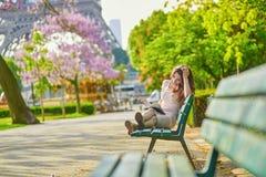 Όμορφη νέα γυναίκα στην ανάγνωση του Παρισιού στον πάγκο υπαίθρια στοκ εικόνες