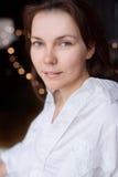 Όμορφη νέα γυναίκα στην ανθρώπινη συνεδρίαση πουκάμισων στο κρεβάτι στοκ φωτογραφίες