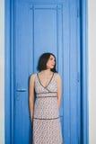 Όμορφη νέα γυναίκα στην εσωτερική μπλε πόρτα Στοκ Φωτογραφίες