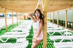 Όμορφη νέα γυναίκα στην ντυμένη χαλάρωση στην πισίνα σαλονιών μονίππων πλησίον Στοκ φωτογραφία με δικαίωμα ελεύθερης χρήσης